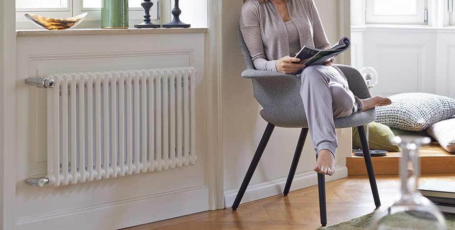 Femme sur sa chaise à côté d'un radiateur pour chauffage central